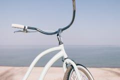 一辆蓝色减速火箭的自行车的特写镜头反对海的海滩的 库存照片