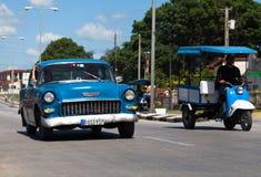 一辆蓝色经典汽车在街道上drived 库存图片