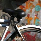 一辆被挂锁的自行车对街道画被绘的墙壁 图库摄影