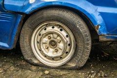 一辆被放弃的蓝色汽车的泄了气的轮胎零件在德波拍的庭院照片停放了印度尼西亚 免版税库存照片