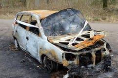 一辆被烧的汽车的击毁在森林里 免版税库存照片