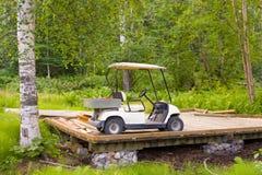 一辆被盖的高尔夫车在一个木甲板停放了 免版税库存照片