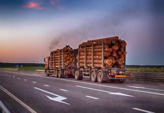 一辆被装载的木材卡车运输与超载的木材日志在高速公路,黑烟 木材的运输的概念 库存照片