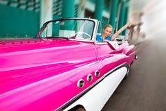 一辆轮子老美国减速火箭的汽车的美丽的妇女在哈瓦那旧城,古巴 库存照片