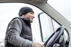 一辆重型卡车的年轻司机有微笑的在轮子后坐 库存照片