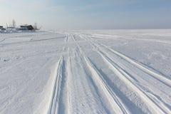 一辆雪上电车的踪影冻水库多雪的表面上的在黎明 免版税图库摄影