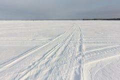 一辆雪上电车的踪影冻水库多雪的表面上的在黎明 免版税库存图片