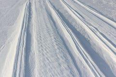 一辆雪上电车的踪影冻水库多雪的表面上的在黎明 图库摄影