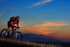 一辆骑自行车的人和自行车的剪影在日落背景 库存照片