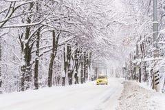 一辆黄色出租汽车沿冬天路乘坐 很多雪 da 免版税库存图片