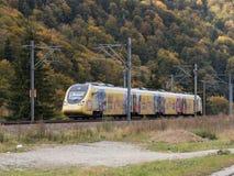 一辆黄色电车,装饰用图画,沿山岭地区移动在锡纳亚市附近在罗马尼亚 图库摄影