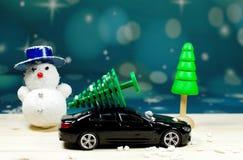 一辆黑汽车运载在汽车屋顶的一棵圣诞树 库存照片