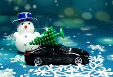 一辆黑汽车运载在汽车屋顶的一棵圣诞树 库存图片