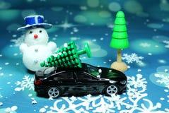 一辆黑汽车运载在汽车屋顶的一棵圣诞树 免版税图库摄影