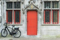 一辆黑自行车在一个老大厦前面停放了 库存图片