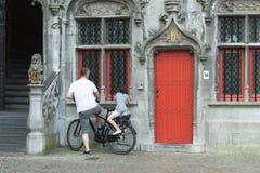 一辆黑自行车在一个老大厦前面停放了 图库摄影