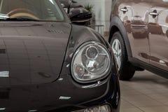 一辆黑跑车的前面的特写镜头视图在一辆小轿车的有一个透明圆的车灯的在经销权中在陈列 库存图片