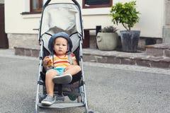 一辆婴儿推车的可爱的儿童小孩在街道上 库存照片