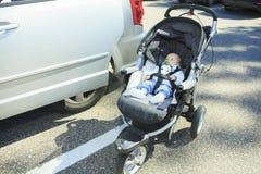 一辆婴儿推车的孤独的婴孩在停车处 库存照片