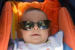 一辆婴儿推车的逗人喜爱的男婴有太阳镜的 免版税库存图片