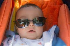 一辆婴儿推车的逗人喜爱的男婴有太阳镜的 图库摄影