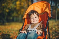 一辆婴儿推车的婴孩在秋天公园 免版税库存照片