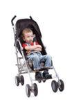 一辆婴儿车的严肃的孩子在白色背景 库存照片