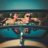 一辆经典敞篷车的两个时髦的夫人 库存照片