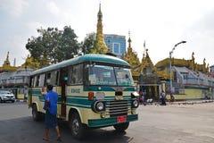 一辆移动的公共汽车和一个步行者在Sule塔前面在街市仰光,缅甸 免版税库存照片