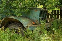 一辆绿色卡车的老生锈的小室长满与草和植被 免版税库存照片