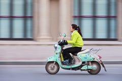 一辆绿色电自行车的时兴的女孩,上海,中国 免版税图库摄影