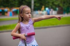 一辆滑行车的可爱的小女孩对于儿童 库存照片