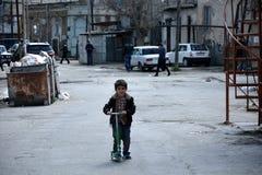 一辆滑行车的年轻男孩在Sovietskaya,巴库,阿塞拜疆的首都的一个恶劣和非现代化的部分 库存图片