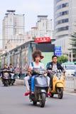 一辆e自行车的凉快的人在市中心,昆明,中国 库存照片