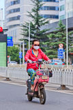 一辆e自行车的妇女在市中心,昆明,中国 免版税图库摄影