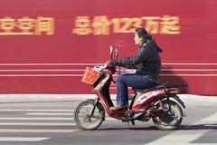 一辆e自行车的妇女有在背景,北京,中国的广告牌的 库存照片