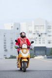 一辆e自行车的妇女有在背景,温州,中国的大厦的 免版税库存照片