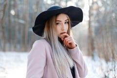 一迷人的俏丽的年轻女人的画象一个黑典雅的帽子的在冬天森林的背景的一件时髦的温暖的桃红色外套 免版税库存照片