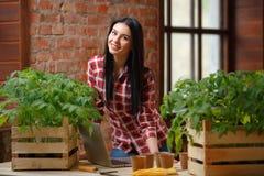 一迷人年轻女性从事园艺的画象 免版税库存照片