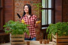 一迷人年轻女性从事园艺的画象 库存图片