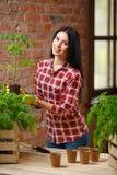 一迷人年轻女性从事园艺的画象 免版税库存图片
