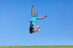 一逗人喜爱少年黑男孩跳跃的室外画象 免版税图库摄影