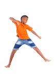一逗人喜爱少年黑男孩跳跃的画象 库存照片
