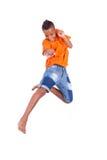 一逗人喜爱少年黑男孩跳跃的画象 免版税库存图片
