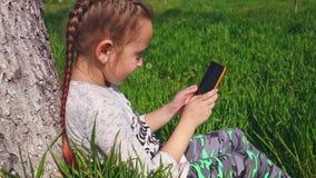 一逗人喜爱的女孩在她的手上坐草在树下并且拿着一个电话 影视素材