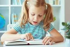 一逗人喜爱的女孩的画象读了书在桌上在教室 免版税库存图片