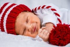 一逗人喜爱的愉快的看起来的可爱的新生儿的接近的顶头照片有红色盖帽的 库存照片