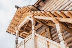 一部分的一个木房子的门面古老样式的 在二楼视图从下面和太阳光芒的美丽的木游廊 免版税库存图片