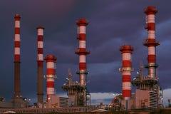 一部分的一个炼油厂的许多烟囱在晚上 免版税库存图片