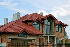 一部分的一个现代砖房子在天空背景的一个铺磁砖的屋顶下 图库摄影